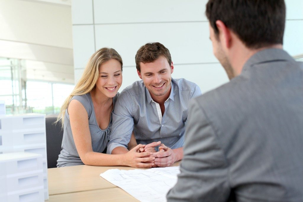 a couple talking to a real estate agent