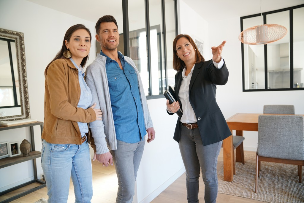 Real estate agent touring the couple in a house