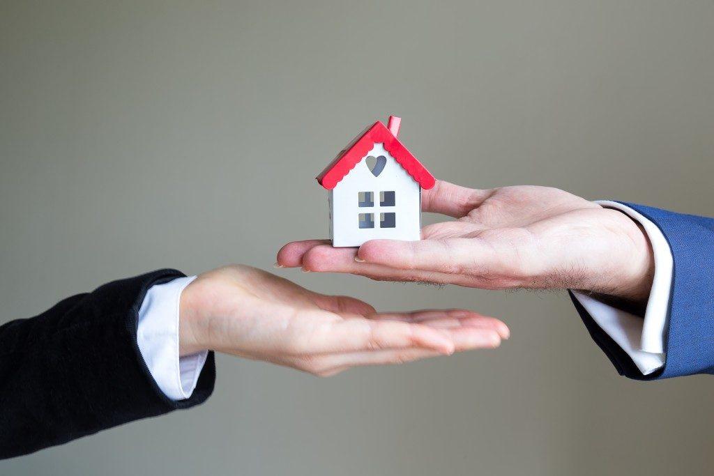 handing a miniature house