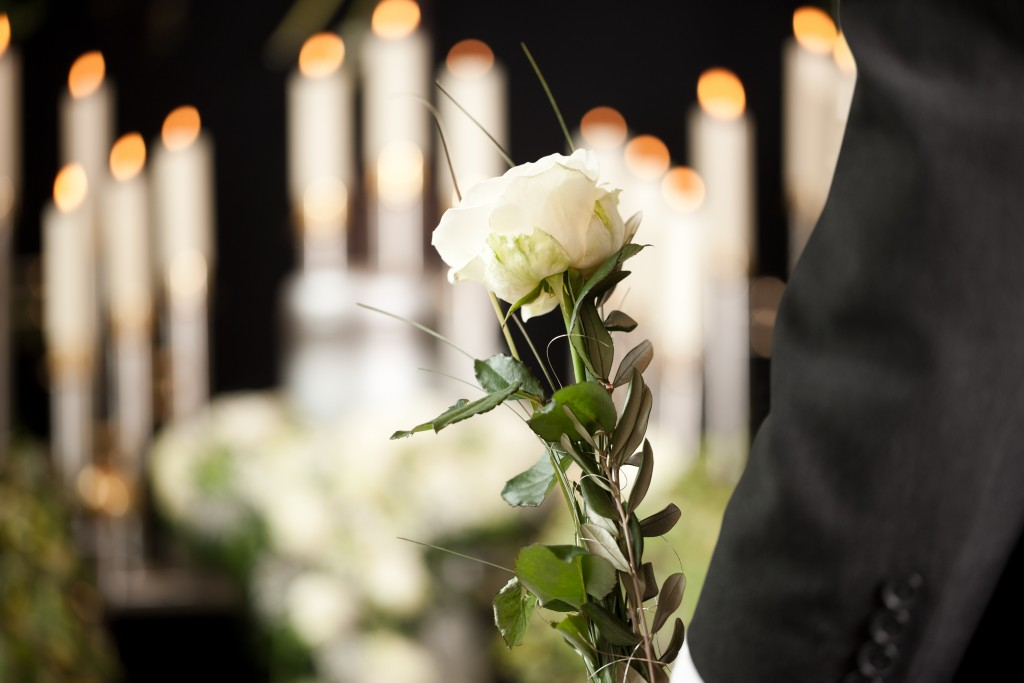 Man holding a white rose in a funeral
