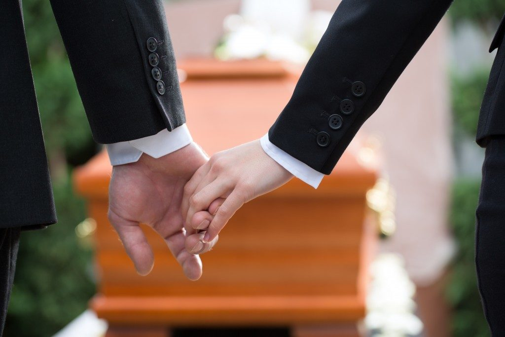 Couple holding hands in front of a coffin