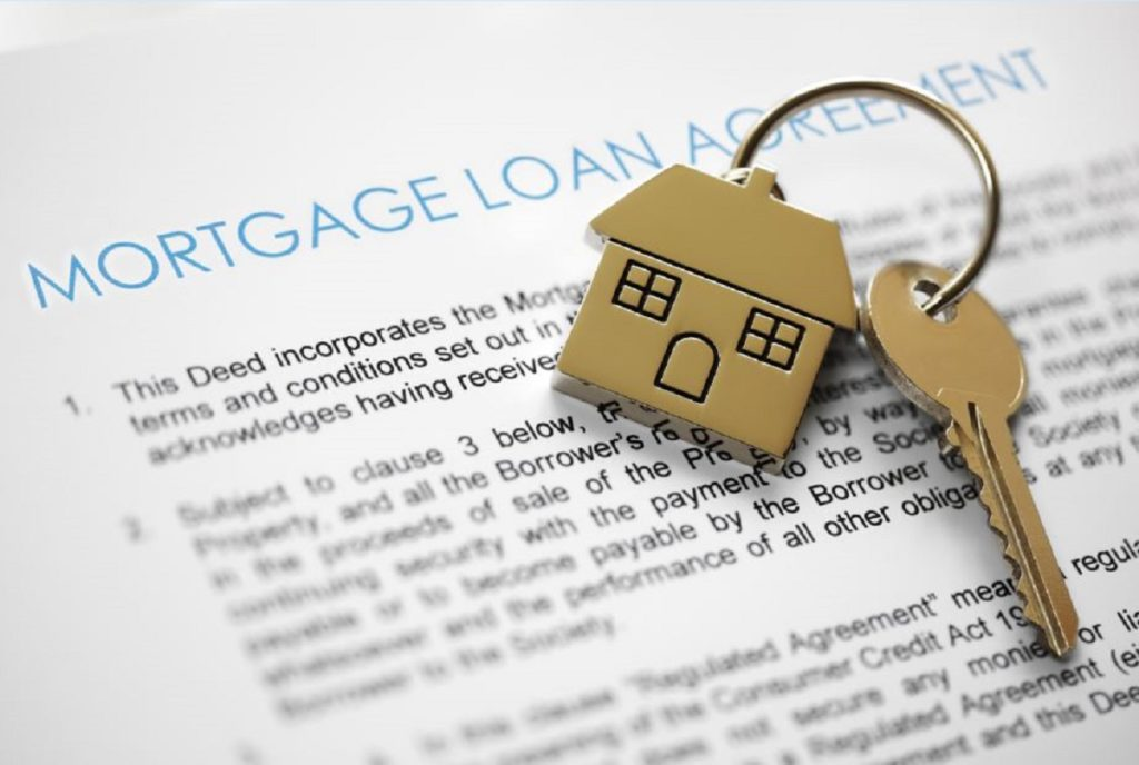 House key on top of a mortgage agreement