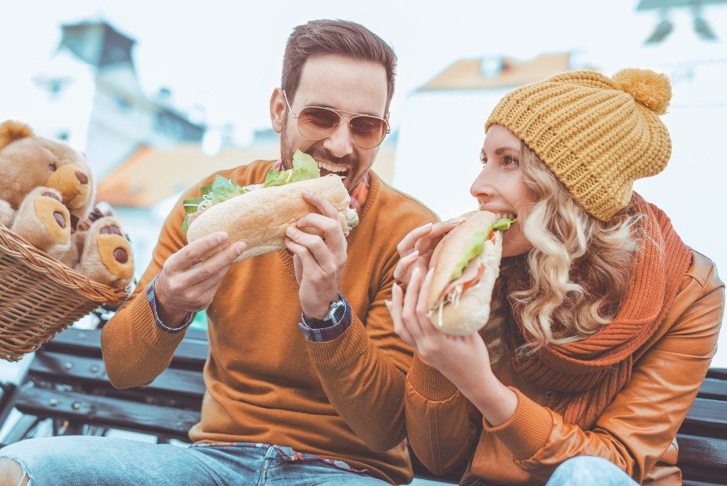 man and woman eating sandwich