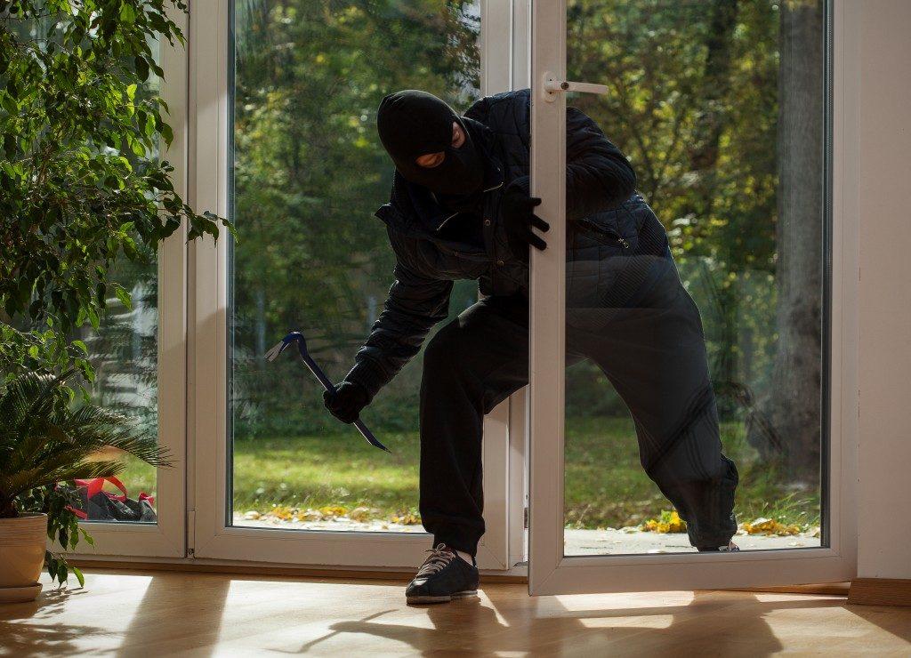 Burglar entering to house through balcony window