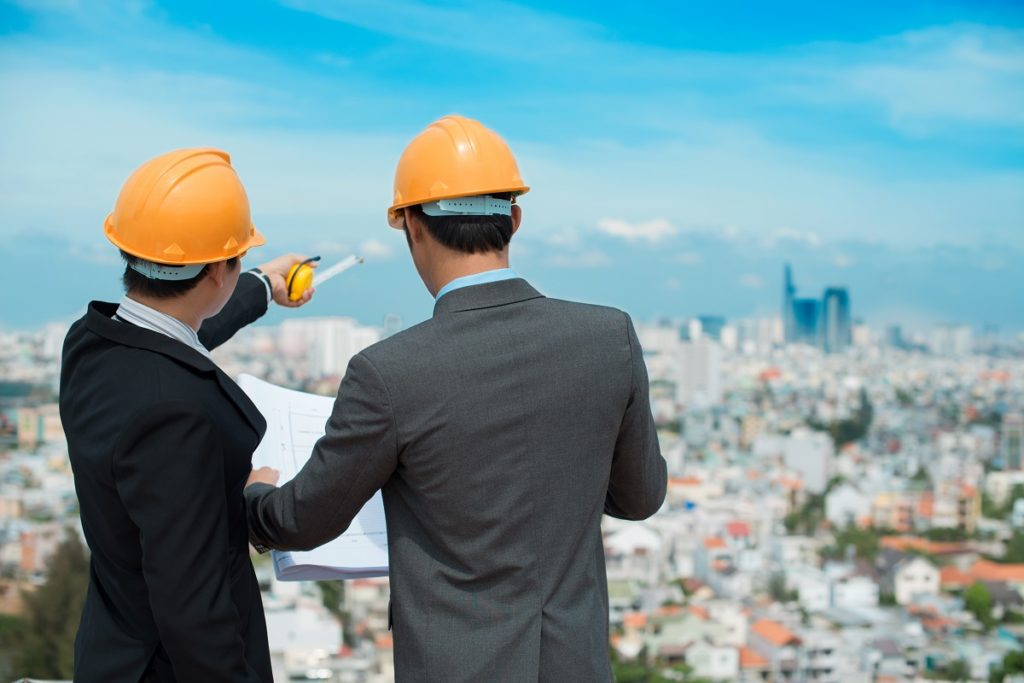 Businessmen in hardhat looking at a blueprint