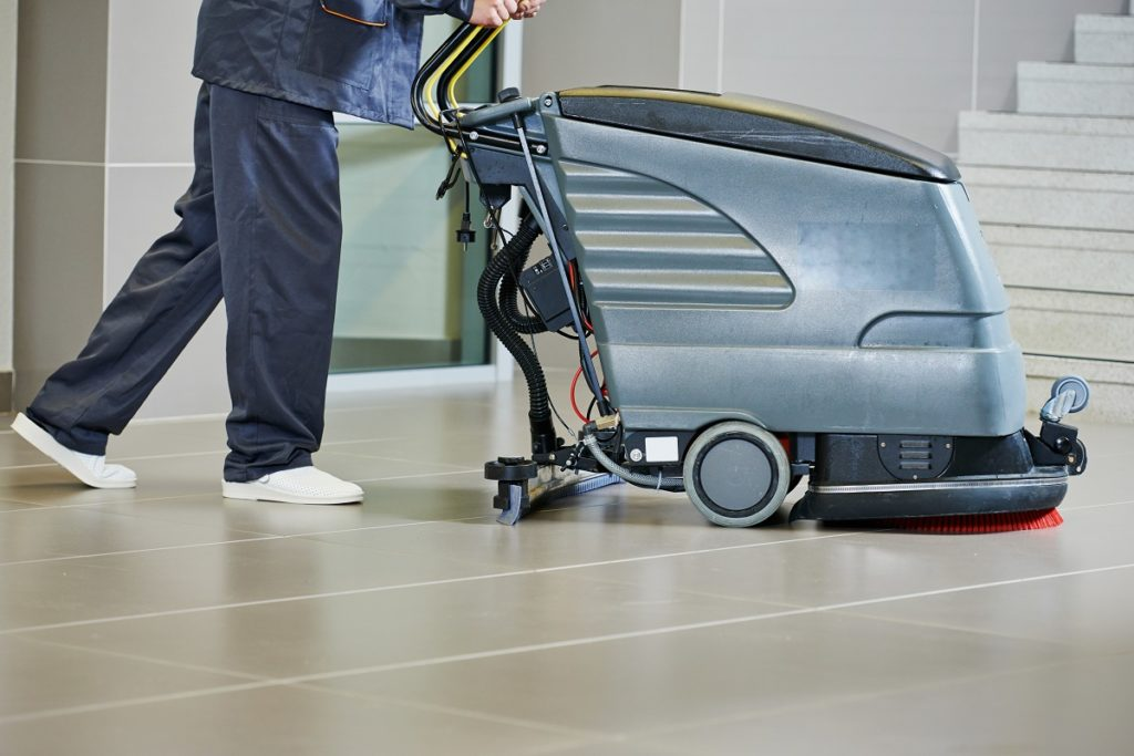 Worker pushing a floor scrubber