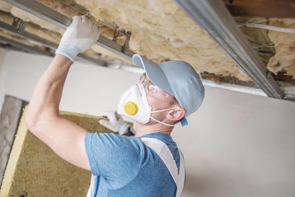 man applying insulation to ceiling