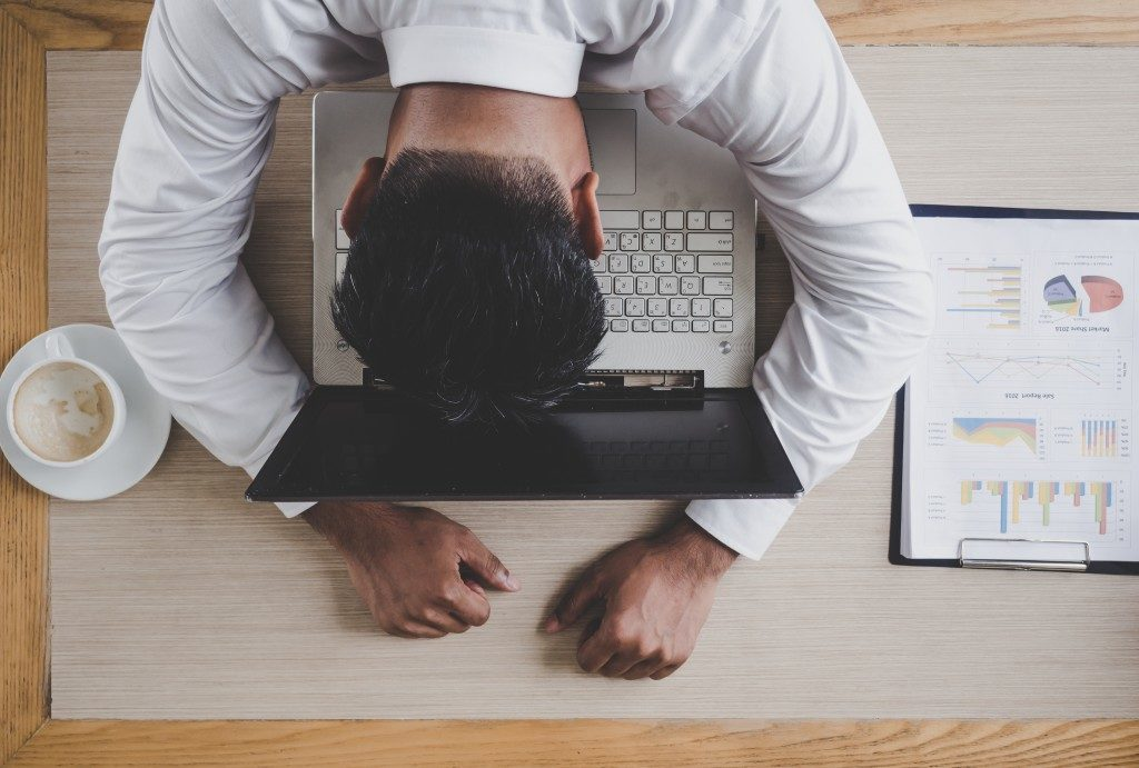 A man laying his head on his laptop