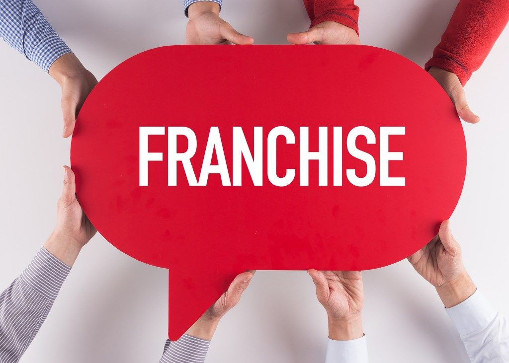 Group of People Holding Franchise Text
