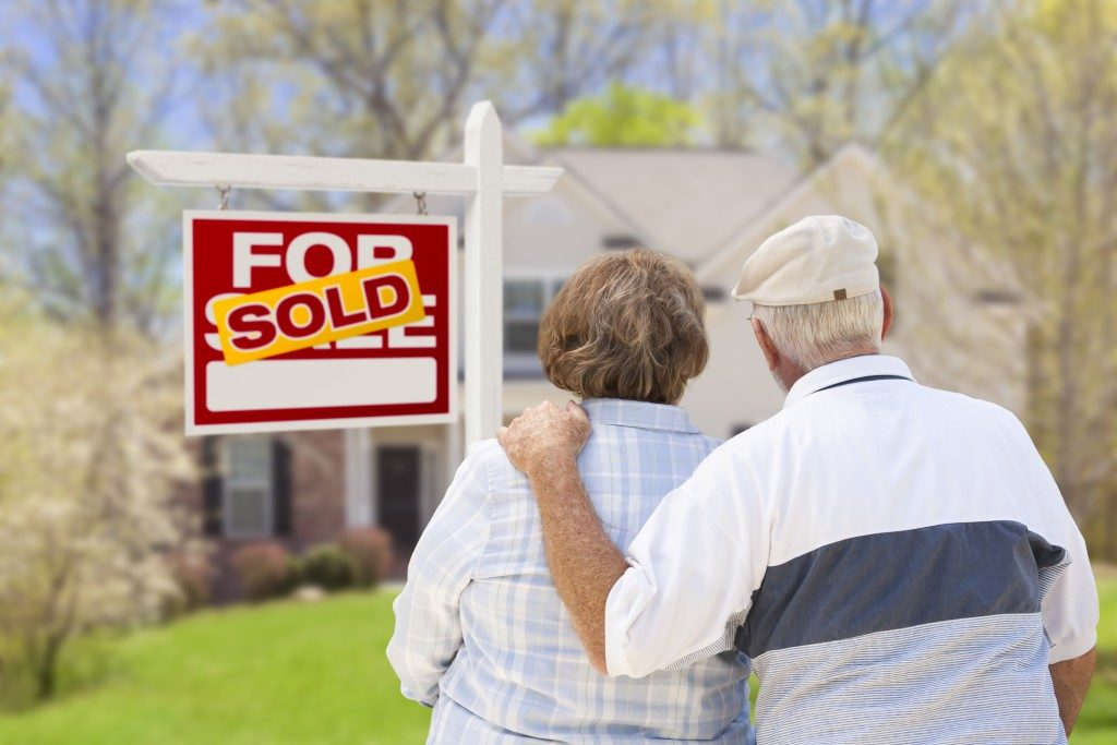 Senior Couple Hugging in Front of Sold Real Estate Sign and House.