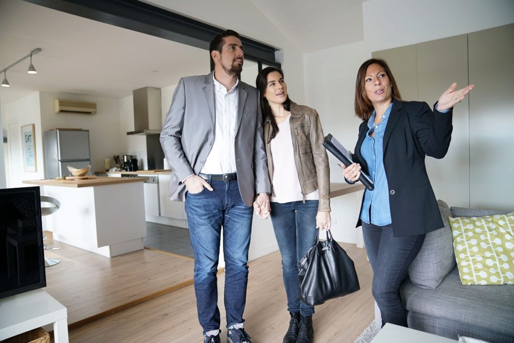 Real estate agent touring the couple inside a home