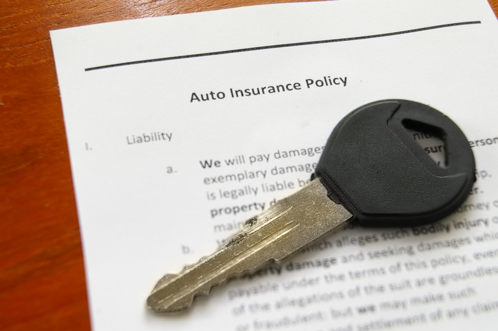 Close up of car key and auto insurance policy