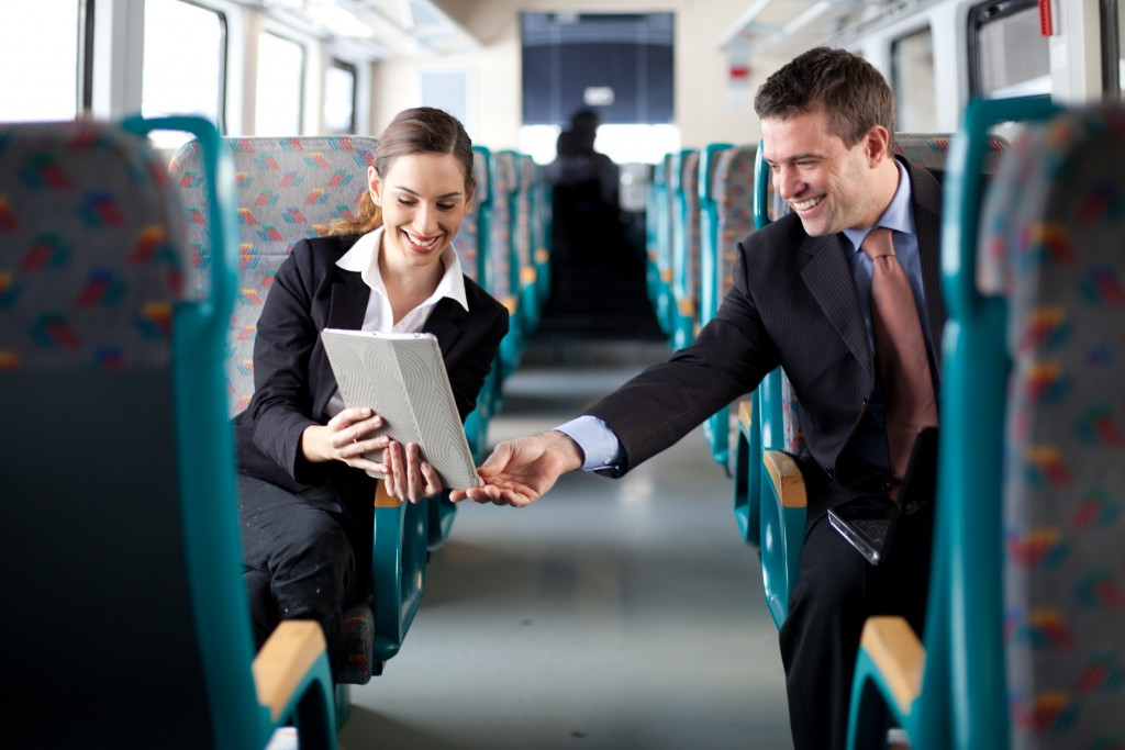 business people working while riding on train