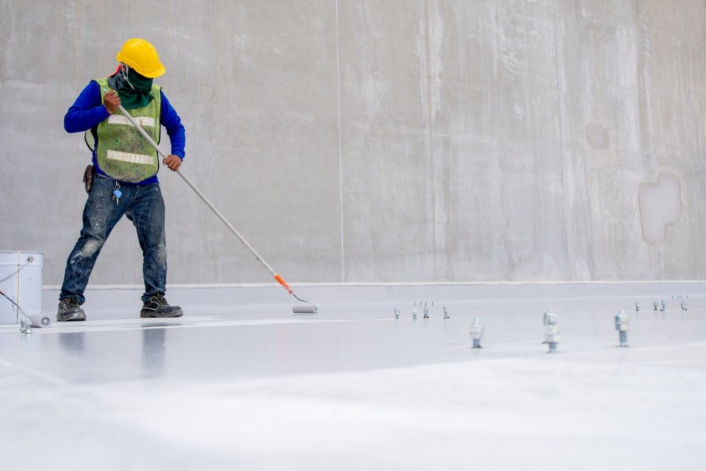 Worker coating the floor with epoxy
