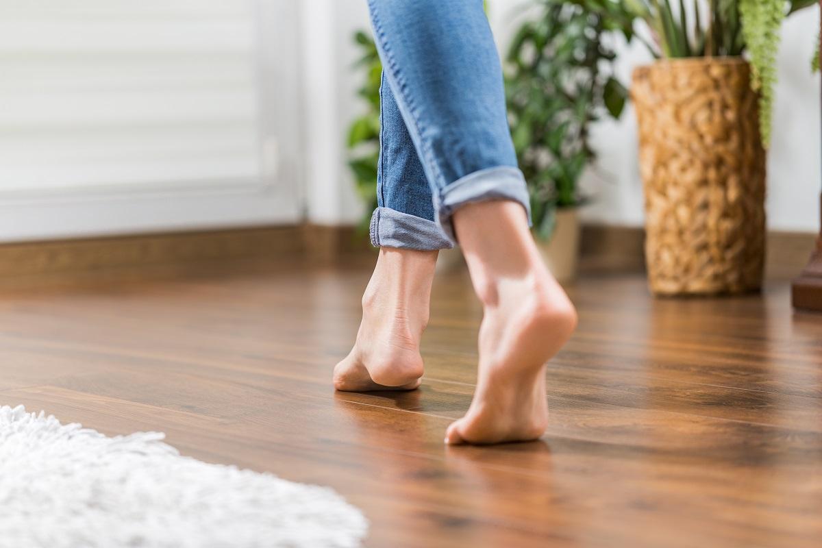 woman walking in the living room's hardwood floor