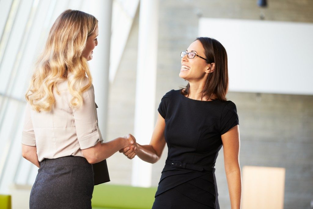 two women giving handshake