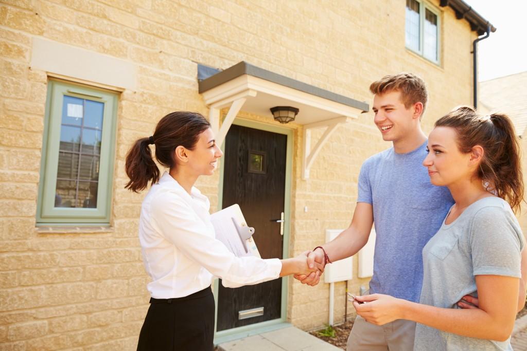 House broker shaking hand of tenants