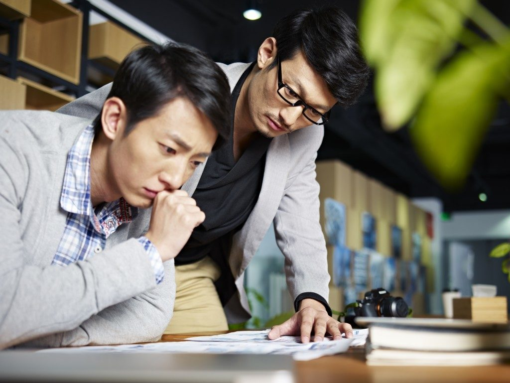 two asian guys looking at a document