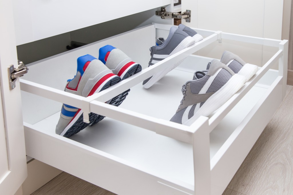 Inner drawer in a cupboard with divider and holder especially for shoes