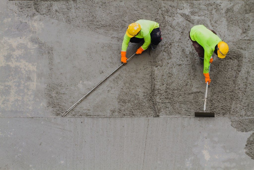 Two men fixing concrete road