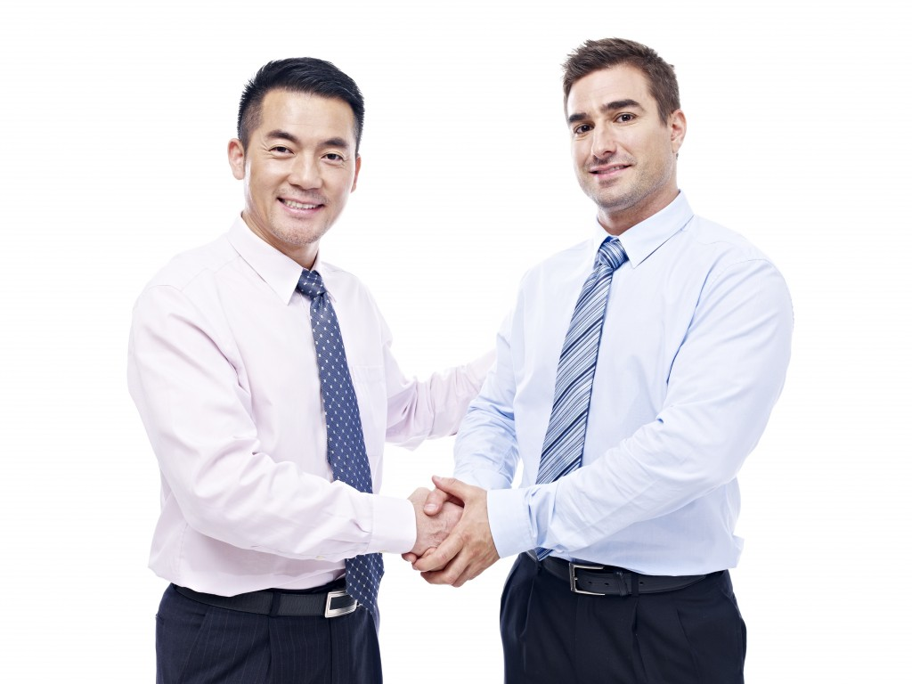 asian and caucasian businessmen shaking hands looking at camera smiling, isolated on white background.