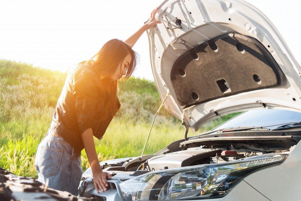 woman checking the engine of her car