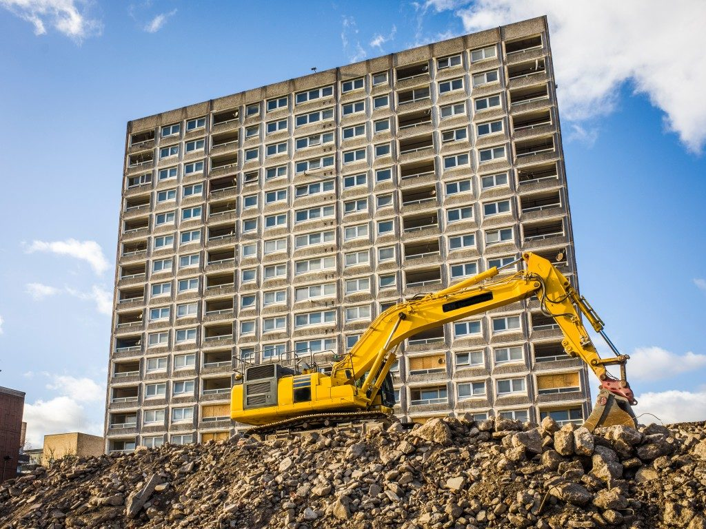 yellow excavator excavating a building