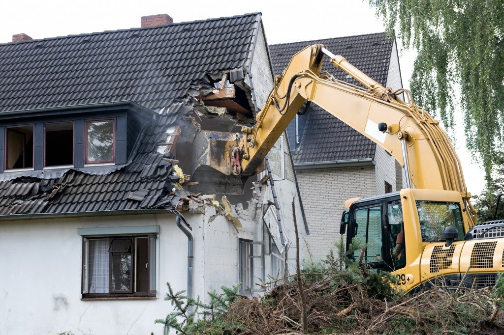 Digger demolishing houses for reconstruction
