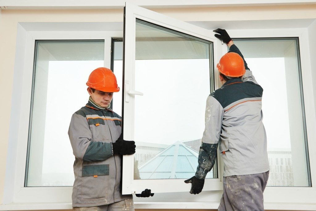male industrial builders workers at window installation