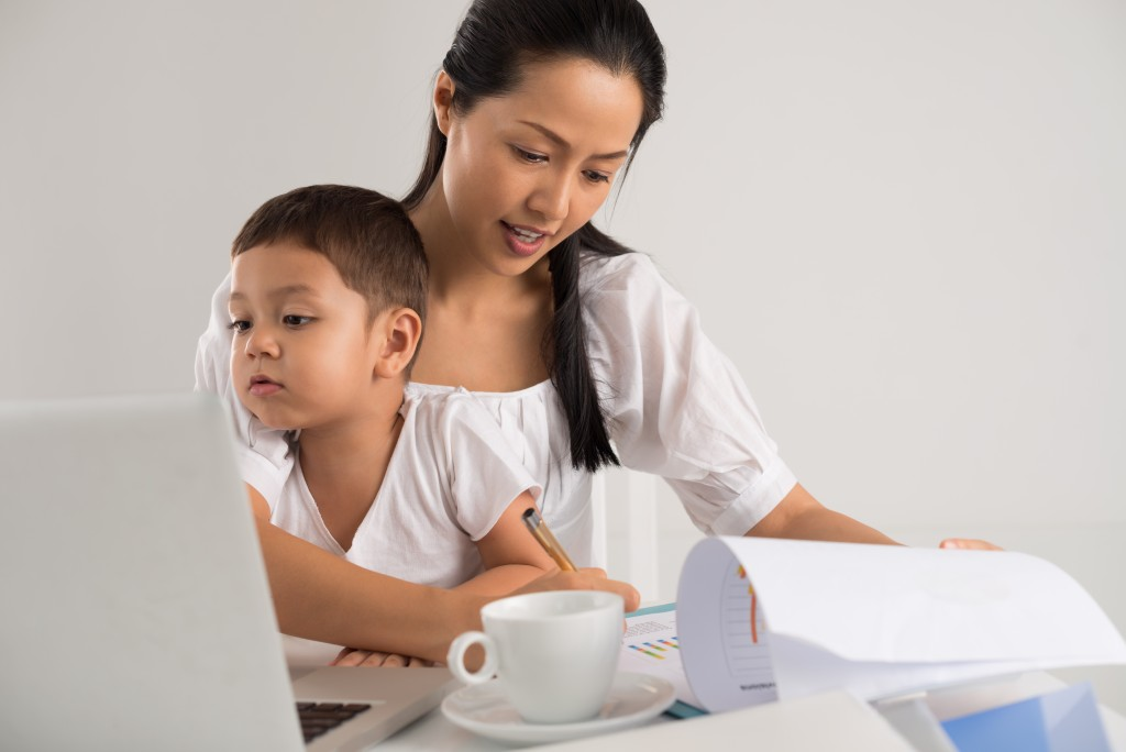 mom working while taking care of her son