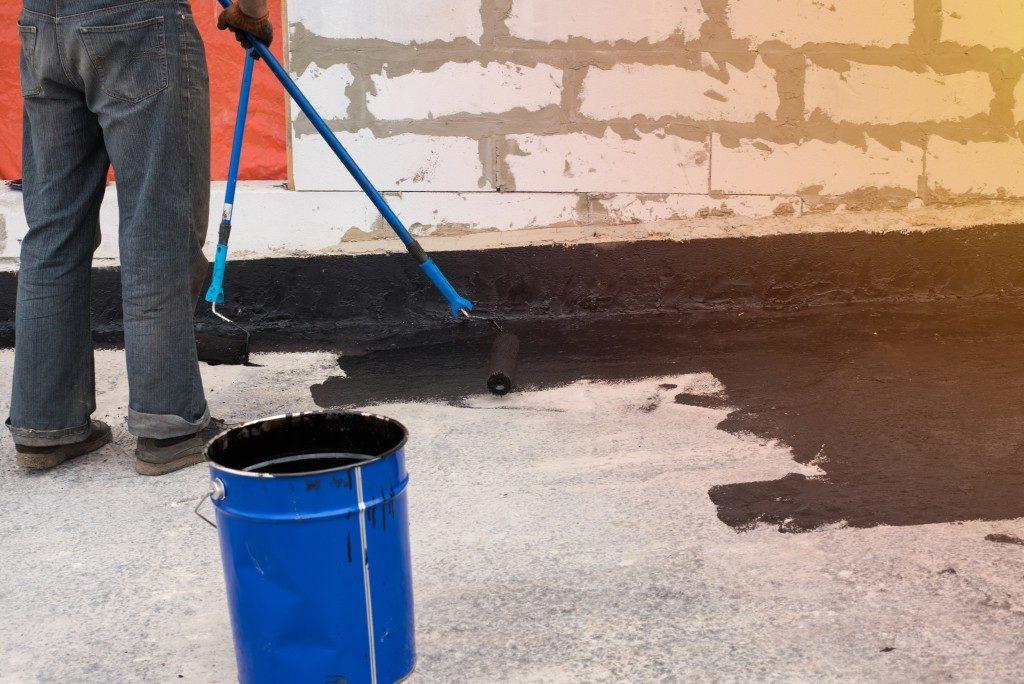 man painting the concrete floor