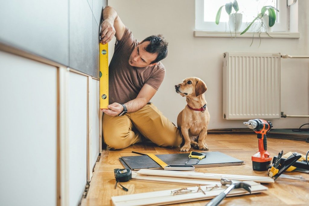 Man measuring wall of home with a dog beside him