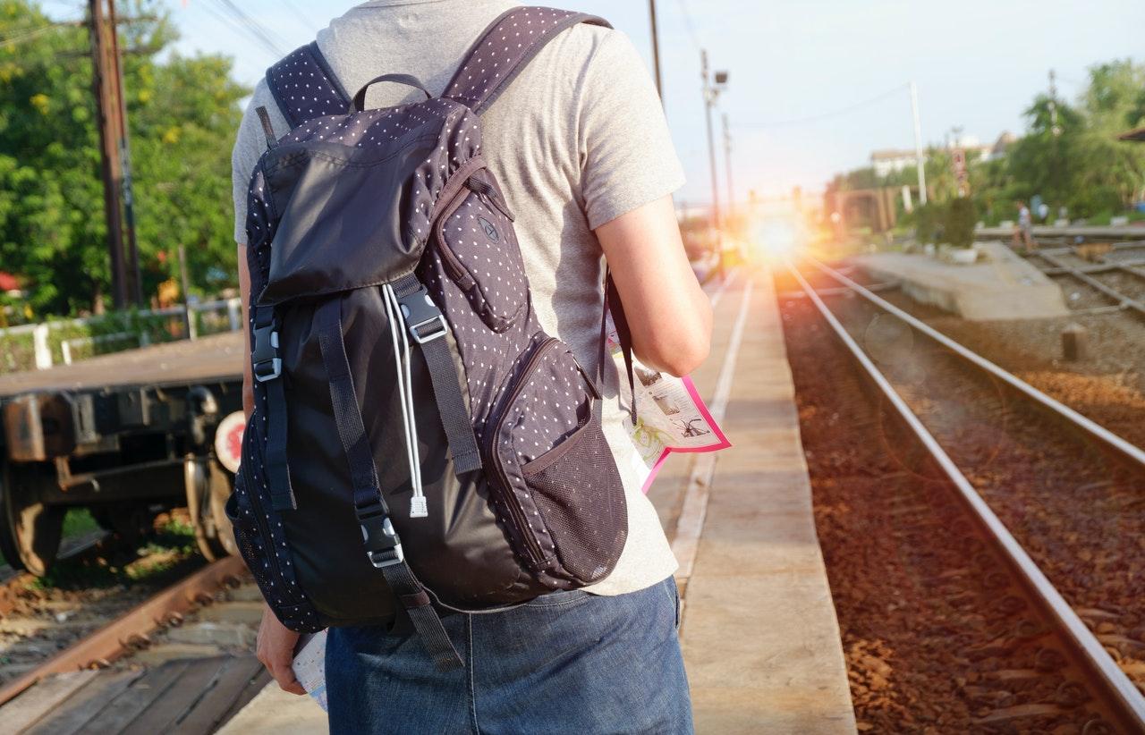 man walking by a railroad