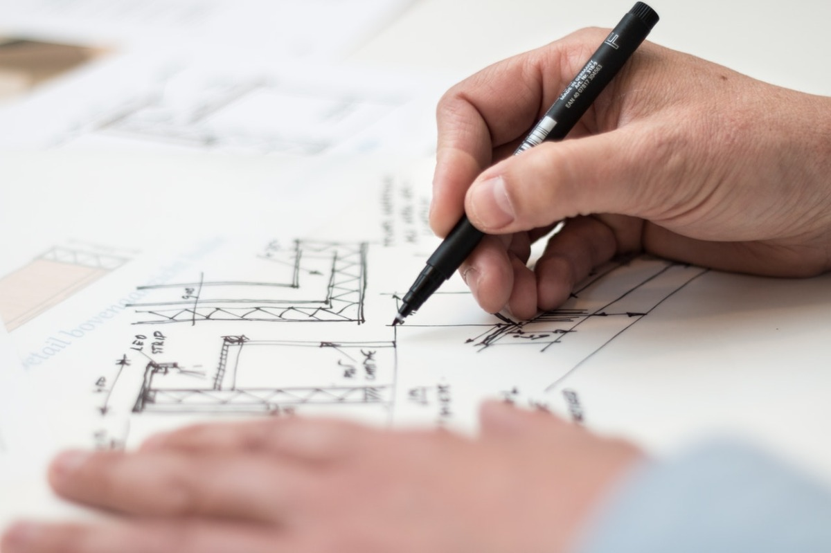 man drawing blueprints